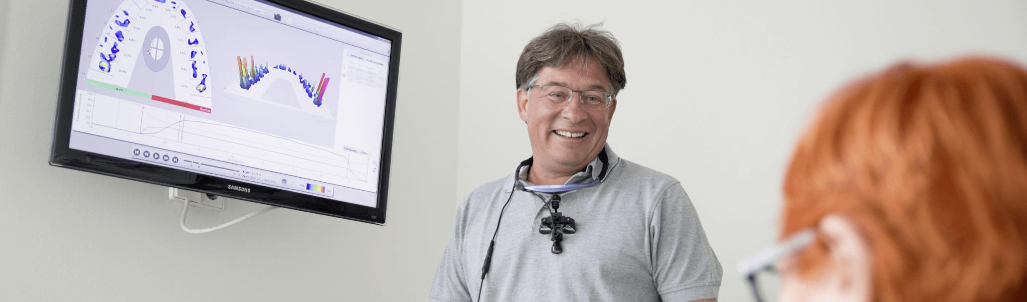 Prophylaxe - Dr. Rentschler lachen mit Patientin im Gespräch, dahinter ein Bildschirm